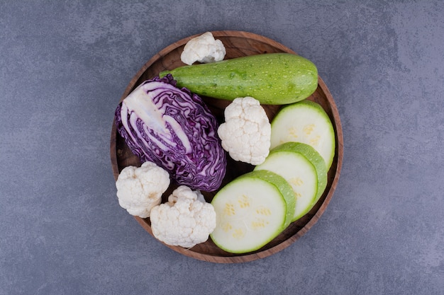 Sliced zucchini, purple cabbage and cauliflowers on a wooden platter.