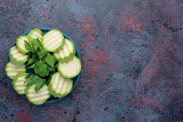 青い大皿にパセリを添えてスライスしたズッキーニ。
