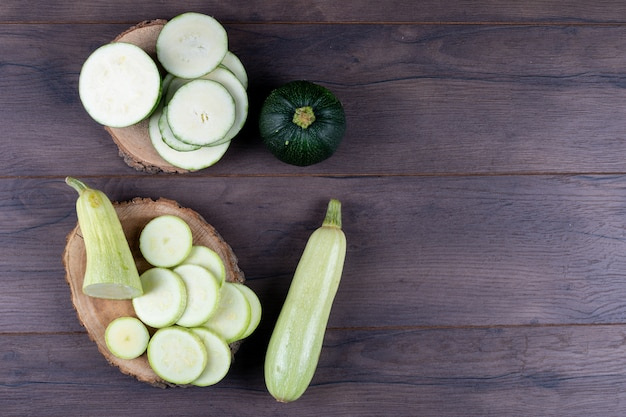Sliced zucchinis on stubs and dark wooden table. top view