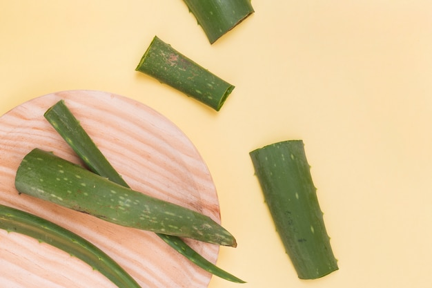 Slices of aloe vera leaves on wooden plate over the yellow background