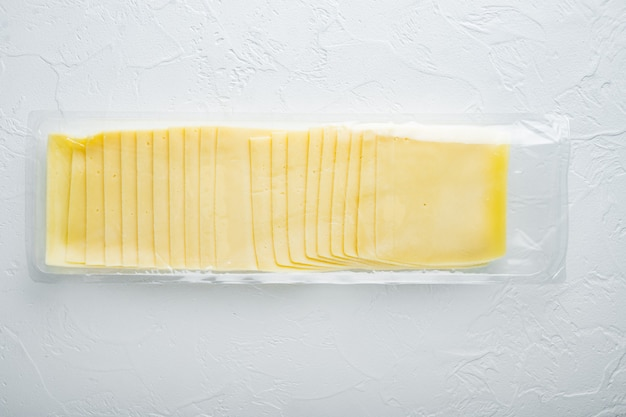 Slices of american cheese in plastic pack, on white table