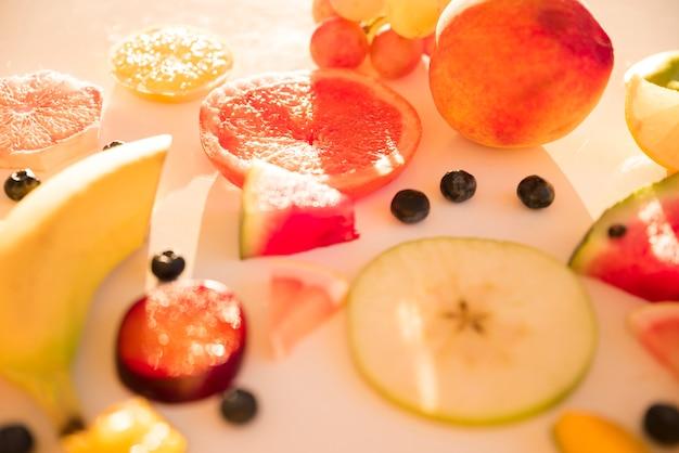 Slices of apple; citrus fruit; plum; grape and blue berries in sunlight