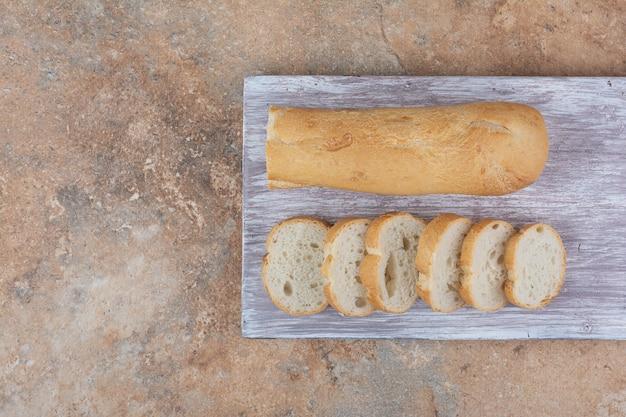 Slices of baguette bread on wooden board