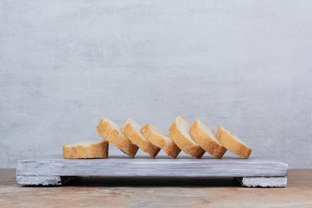 Slices of baguette bread on wooden board