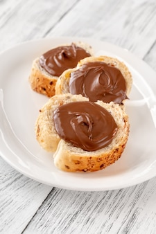 Slices of baguette with chocolate paste on white plate