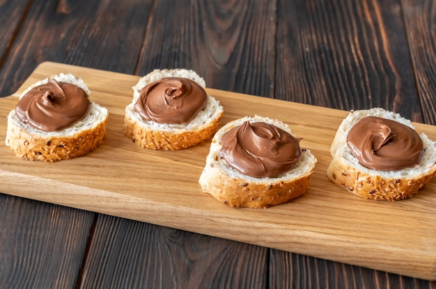 Slices of baguette with chocolate paste on wooden board