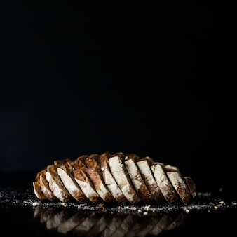 Slices of baked bread against black background