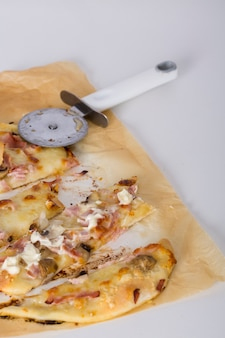 Slices of baked pizza with cutter on parchment paper