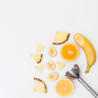 Slices of banana; pineapple; halved oranges with hand blender on white background