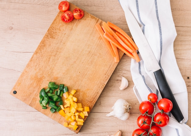 Slices of bell peppers; carrot; halved tomatoes on chopping board with garlic bulb; knife and napkin over the wooden desk