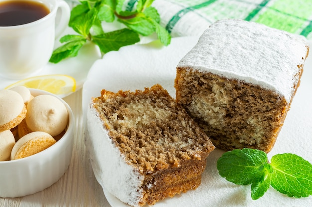 Slices of biscuit cake, a cup of tea with lemon, small cookies and mint leaves on a white wooden table.