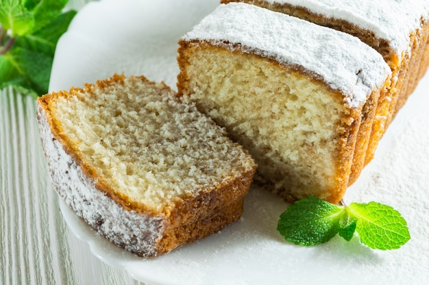 Slices of biscuit cake with powdered sugar, decorated with mint leaves on a white wooden table.