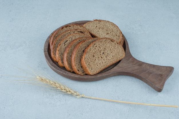 Fette di pane nero sulla zolla blu con grano