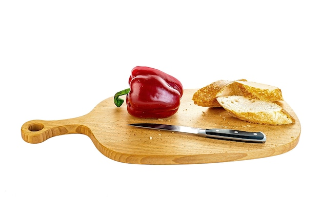 Slices of bread and pepper on a wooden board on the table.