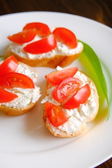 Slices of bread, sandwiches, tomatoes, cheese, on a plate. organic farm products.