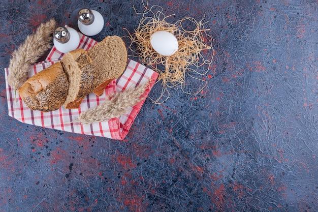 Fette di pane su un asciugamano accanto all'uovo sodo, su sfondo blu.