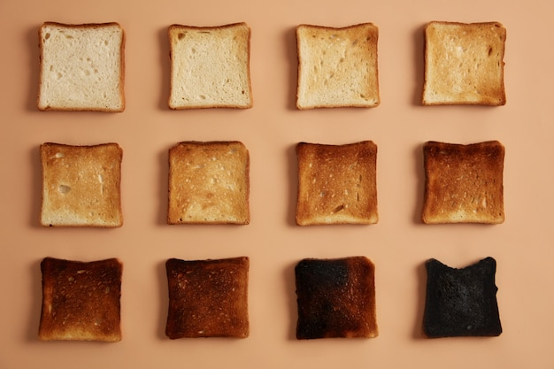 Slices of bread of various degree of toastiness arranged in rows against beige background. toast or snack for eating. stages of toasting. healthy eating, munchies and dieting concept. studio photo