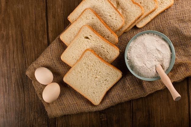 Fette di pane con ciotola di farina e uova