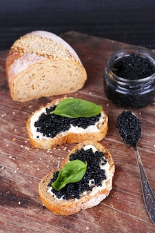 Slices of bread with butter and black caviar on wooden table