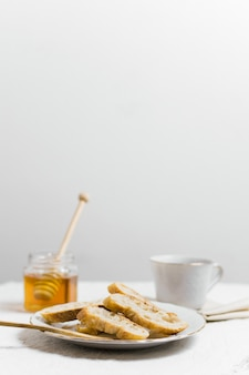 Slices of bread with cup of tea and honey