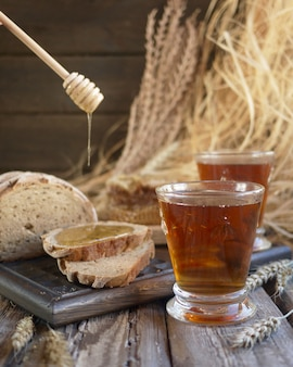 Slices of bread with honey and tea in glasses. village background