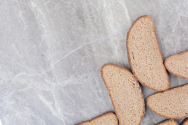 Fette di pane integrale sulla superficie in marmo