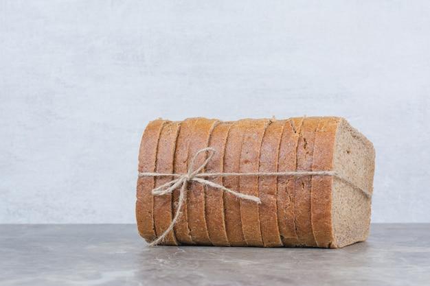 Fette di pane integrale in corda sulla superficie in marmo