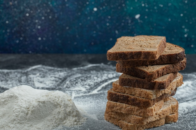Slices of brown bread with flour on a colorful background.
