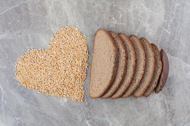 Fette di pane integrale con chicchi di avena sulla superficie in marmo
