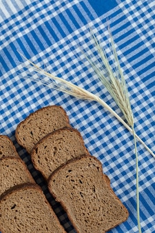Slices of brown bread with wheat on a tablecloth.