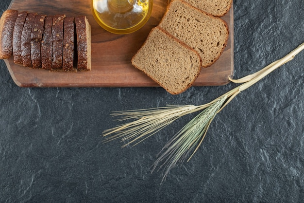 Slices of brown bread with wheat on wooden board.