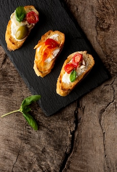 Slices of bruschetta on black wooden board