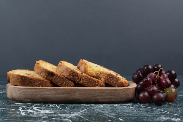 Slices of cake with raisins and grapes on marble background. high quality photo