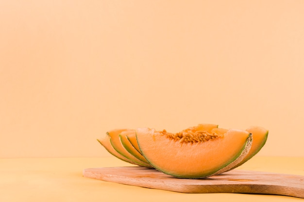 Slices of cantaloupe fruits on chopping board against colored backdrop