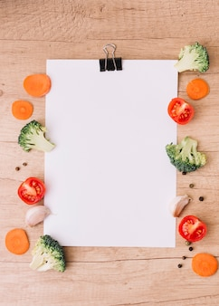 Slices of carrot; halved broccoli; tomatoes; garlic clove and black pepper on the side of blank white paper over the wooden desk