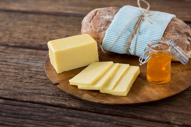 Slices of cheese, bread and fruit jam on wooden board