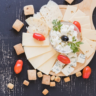 Slices of cheese on chopping board surrounded with tomatoes and pastries on black textured backdrop