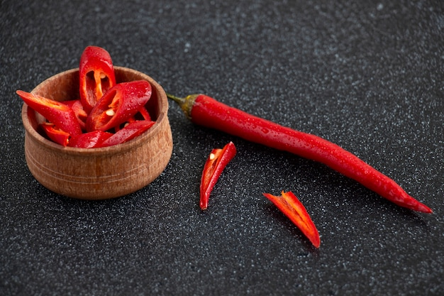 Slices of chili pepper and one whole pepper with water drops in the little wooden plate