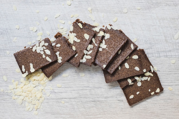 Slices of chocolate bars and almonds on white wooden textured backdrop