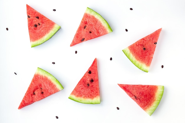 Slices of chopped watermelon with seeds isolated on white