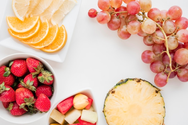 Slices of citrus fruit; strawberry; pineapple; watermelon and grapes on white backdrop