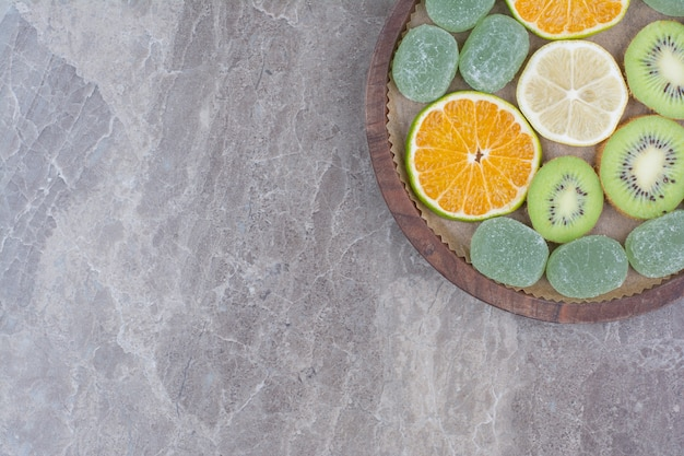 Slices of citrus fruits, kiwi and candies on wooden board.
