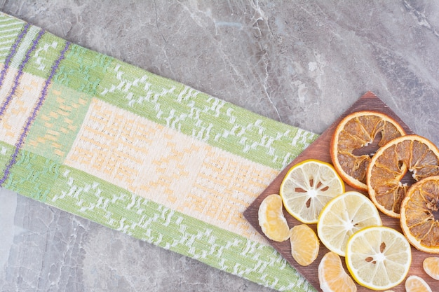 Slices of citrus fruits on wooden board with tablecloth.