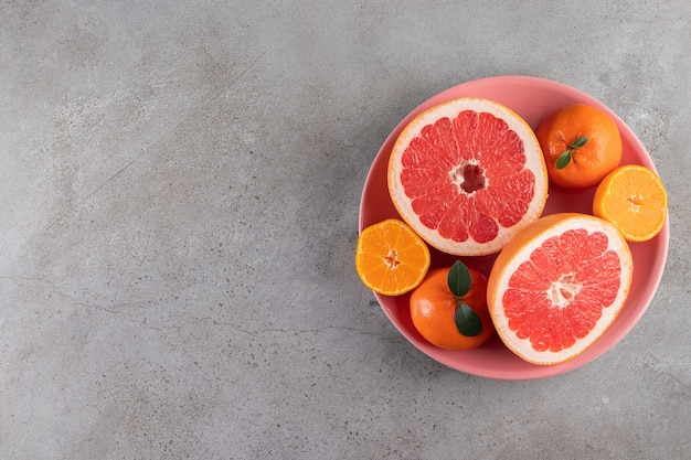 Slices of citrus orange and grapefruit fruits placed on a pink bowl