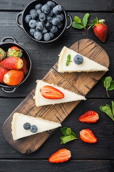 Slices of classical new york cheesecake, on black wooden table background, top view flat lay