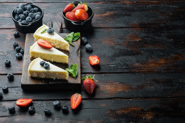 Slices of classical new york cheesecake, on old dark  wooden table background with copy space for text