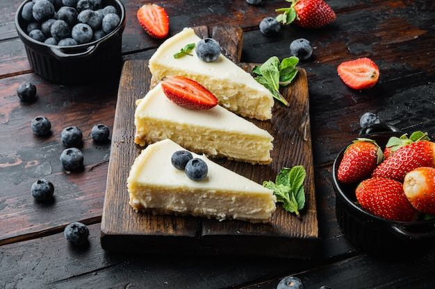 Slices of classical new york cheesecake, on old dark  wooden table background