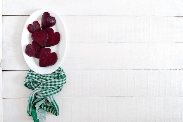 Slices of cooked beets in the shape of a heart on a white plate and a green kitchen towel on a white wooden background. to love beets. copy space