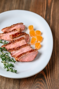 Slices of duck breast with fresh thyme