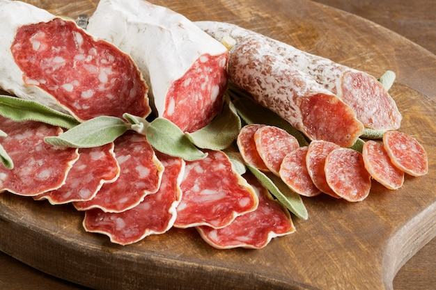 Slices of french cheese-dried salami with spices on wooden background
